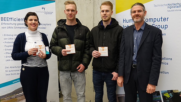 Prof. Dr. Andreas Riener (right), two of the winners (middle), Martina Schuß (left) handing over the vouchers. Source: THI