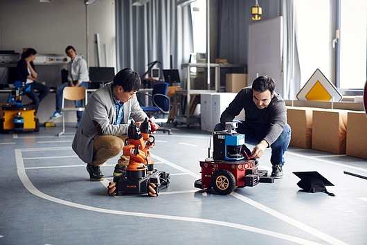 Two graduates testing robots at the lab for robotics.
