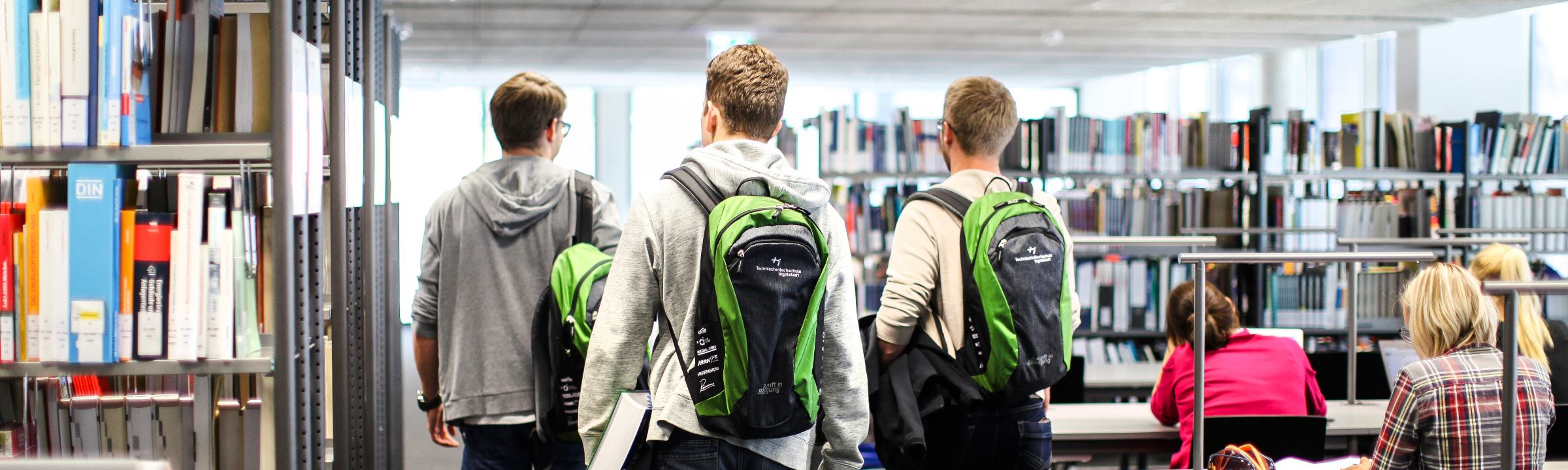 3 students with THI-rucksack walk through the library