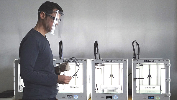Person with face shield in front of 3D printer