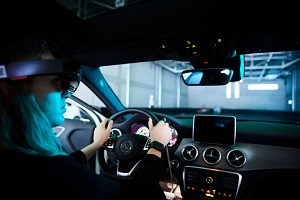 A student wearing virtual reality glasses sits in a test car a