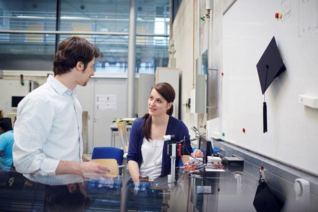 Two doctoral students discuss technical equipment in the laboratory