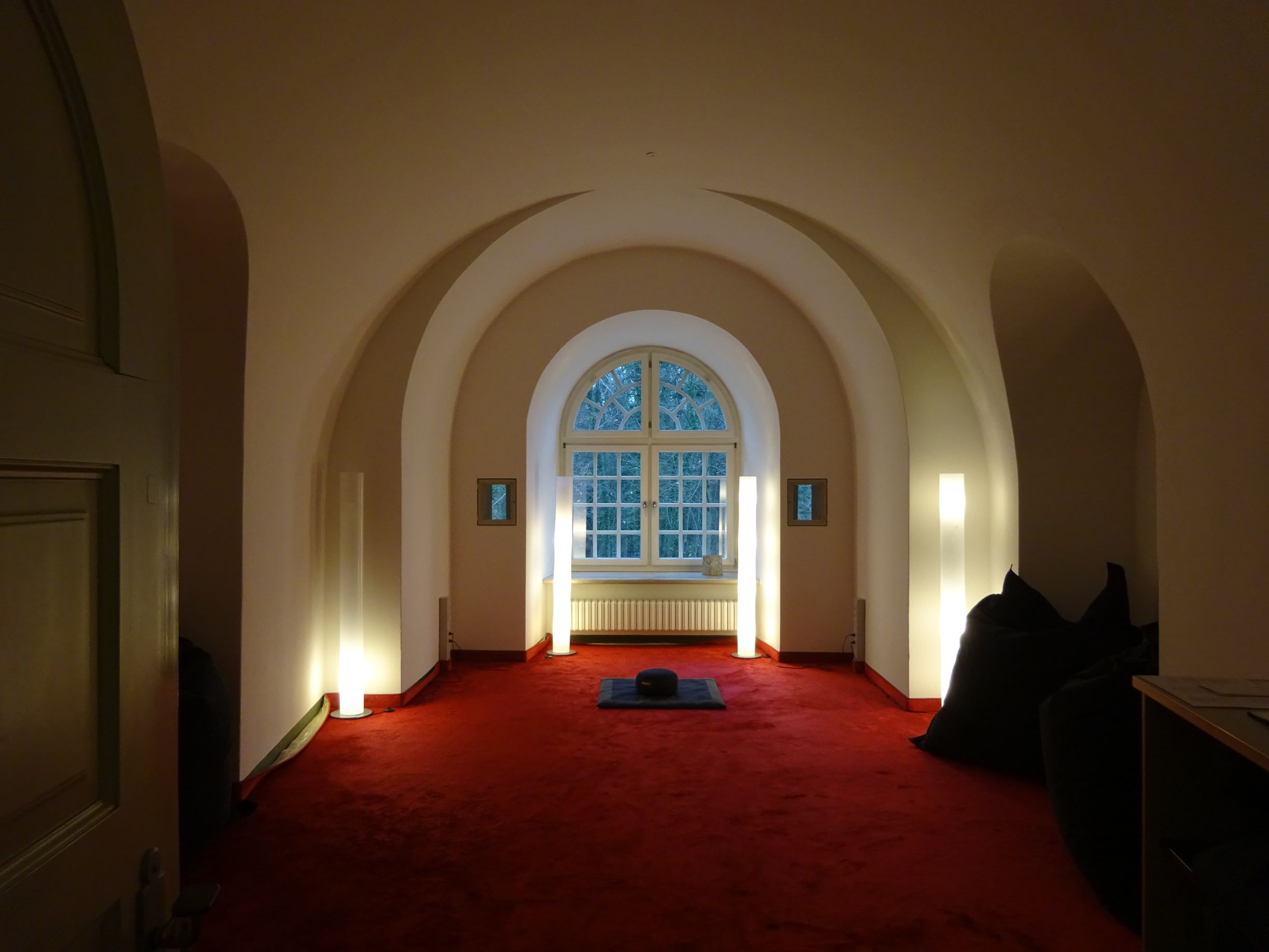 A discreetly lit room with red carpet and high arched window